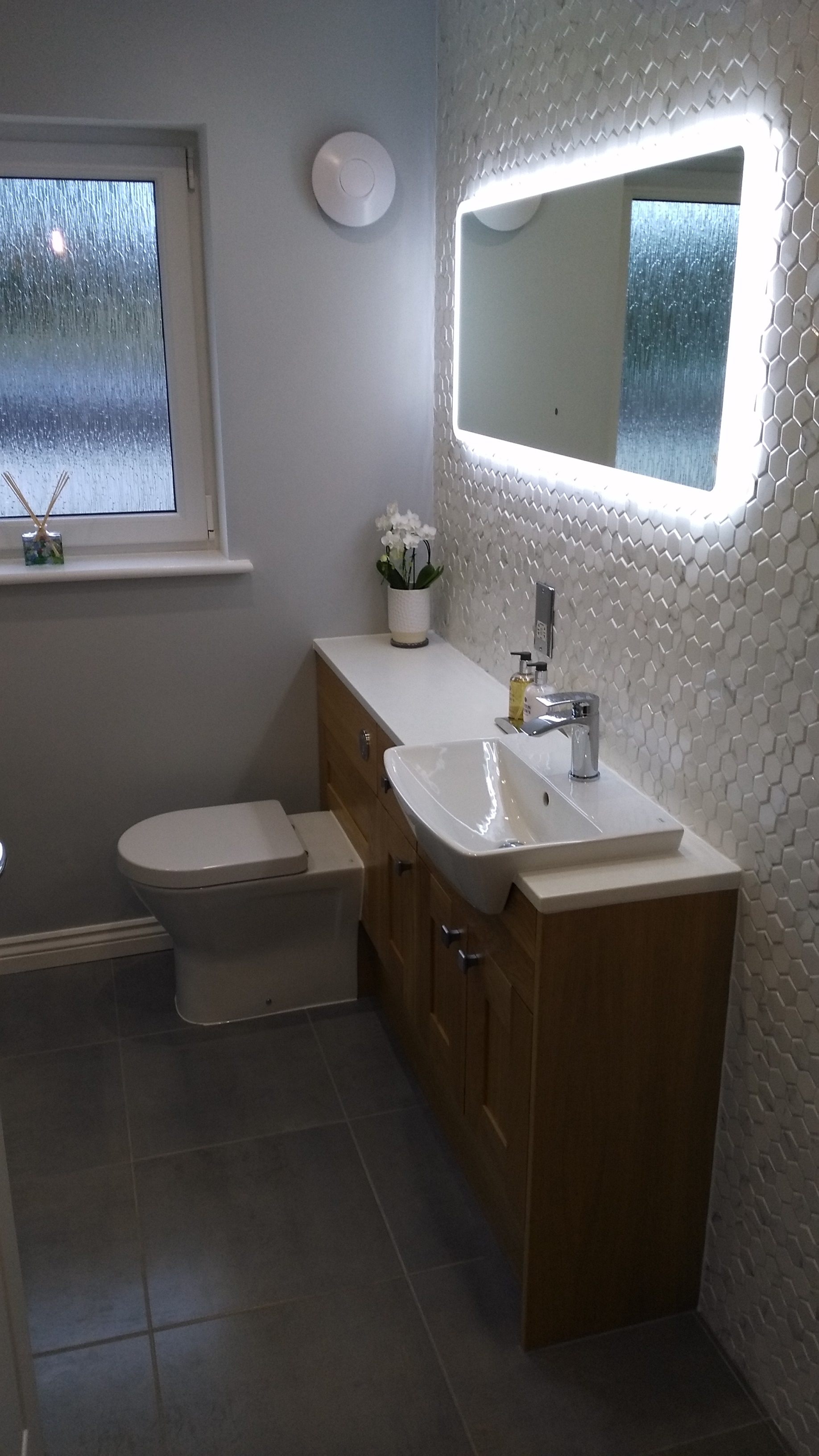 Hexagon Tiles in white gloss with traditional oak vanity unit.