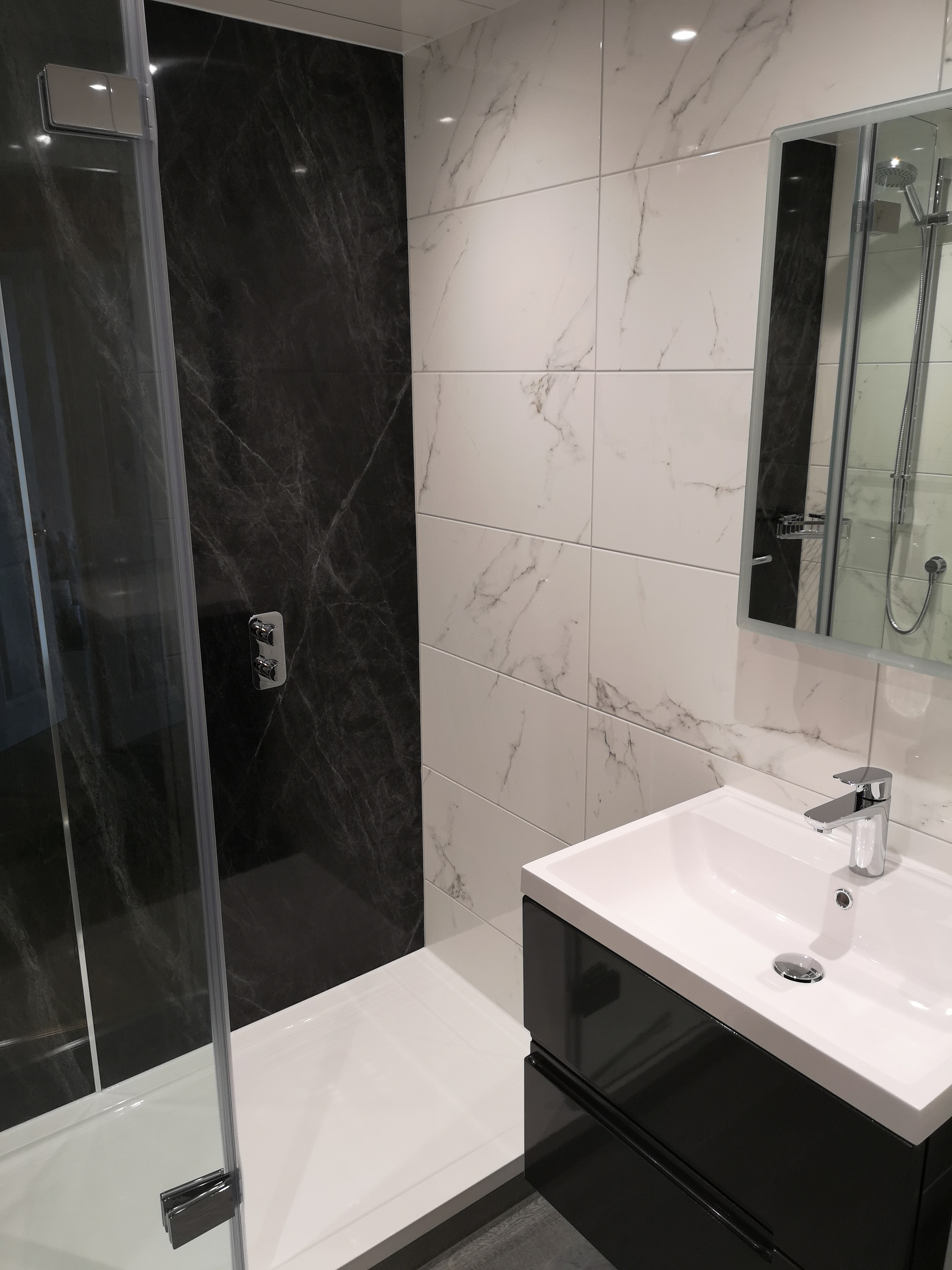 Larger shower with marble tiles and black wet wall panel.