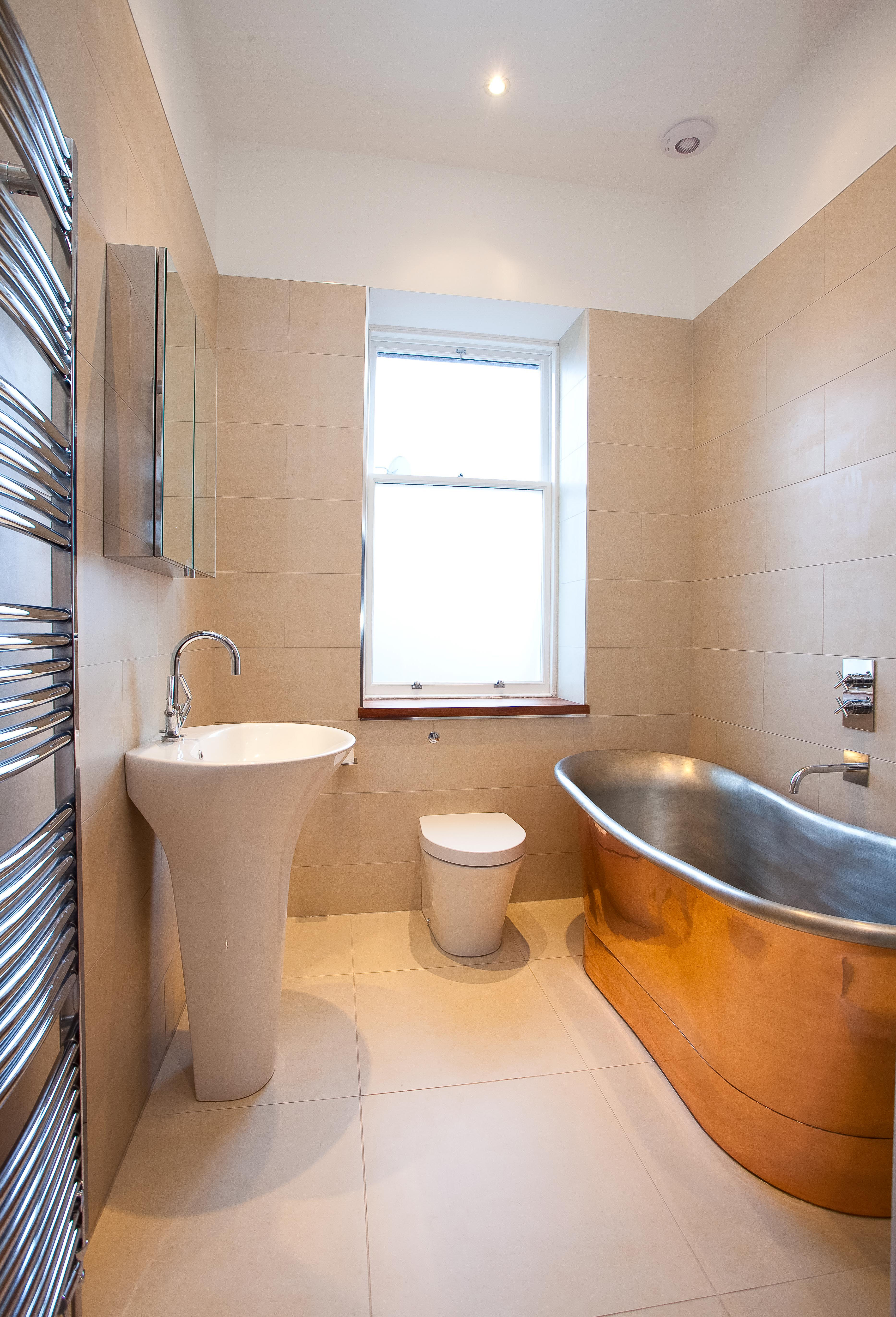 Freestanding Copper Bath with roll top edges, pedestal sink and toilet.