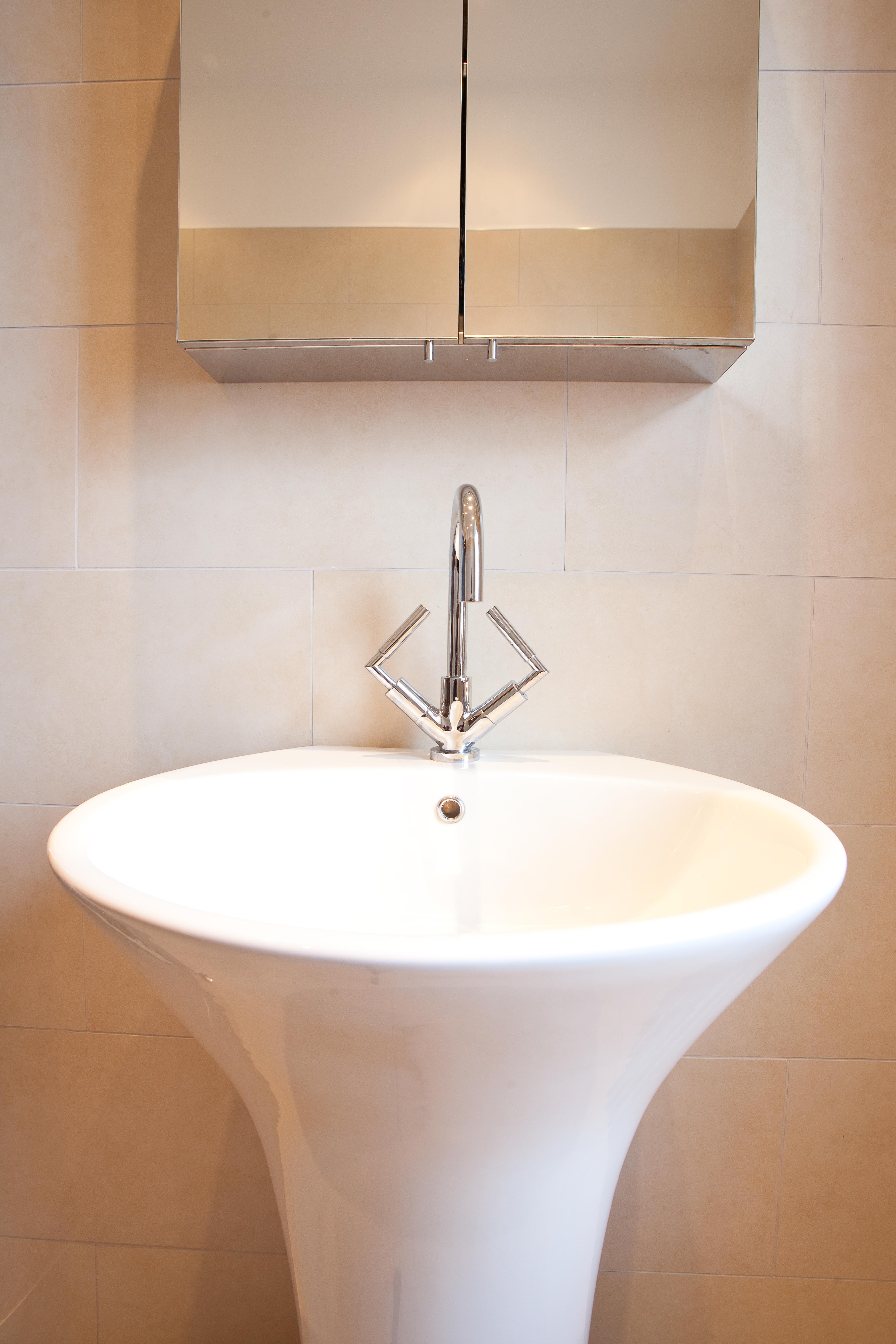 Pedestal bathroom basin with mixer tap and mirror.