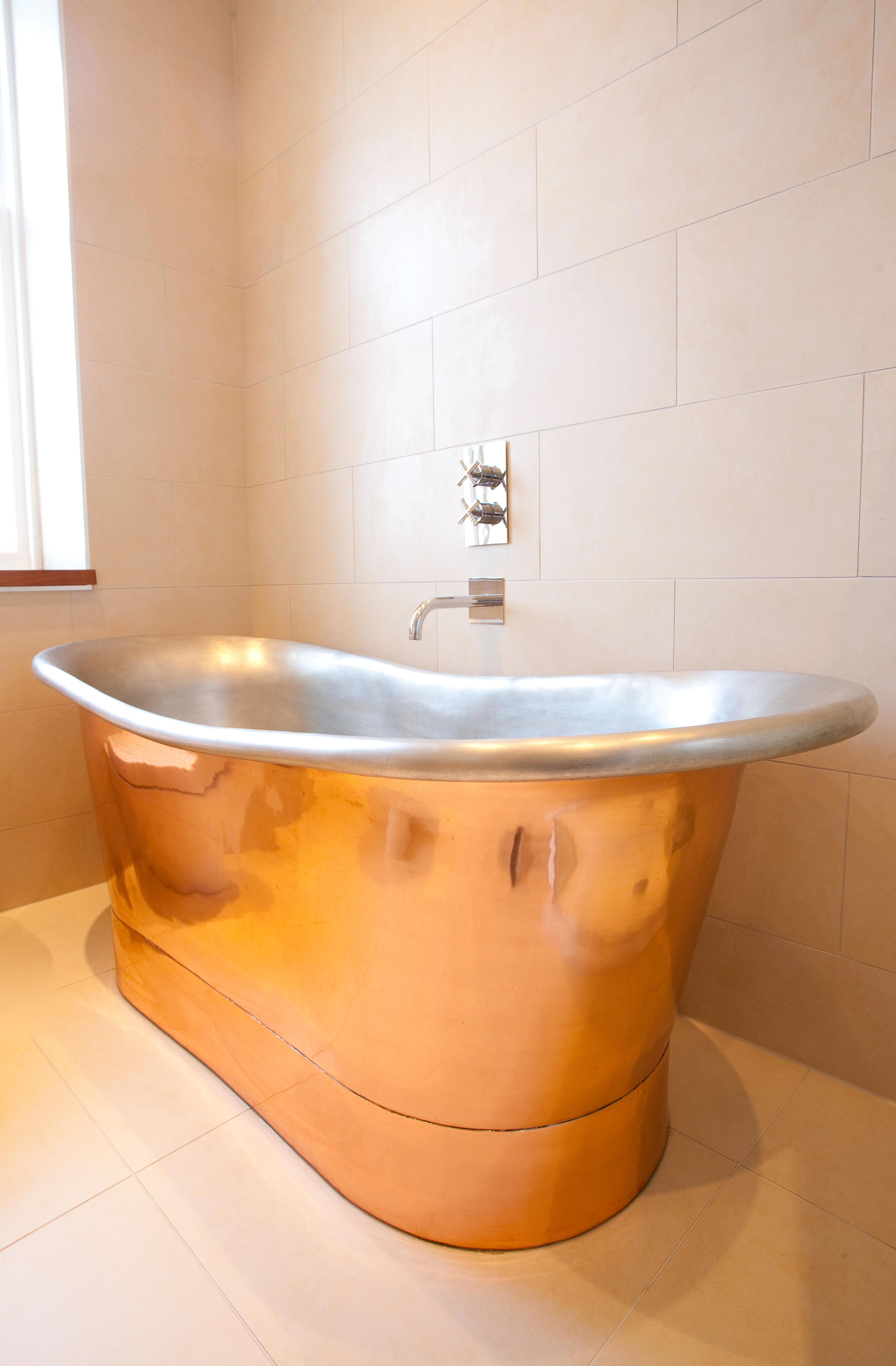 Freestanding Copper Bath with roll top edges and wall mounted tap in Edinburgh.