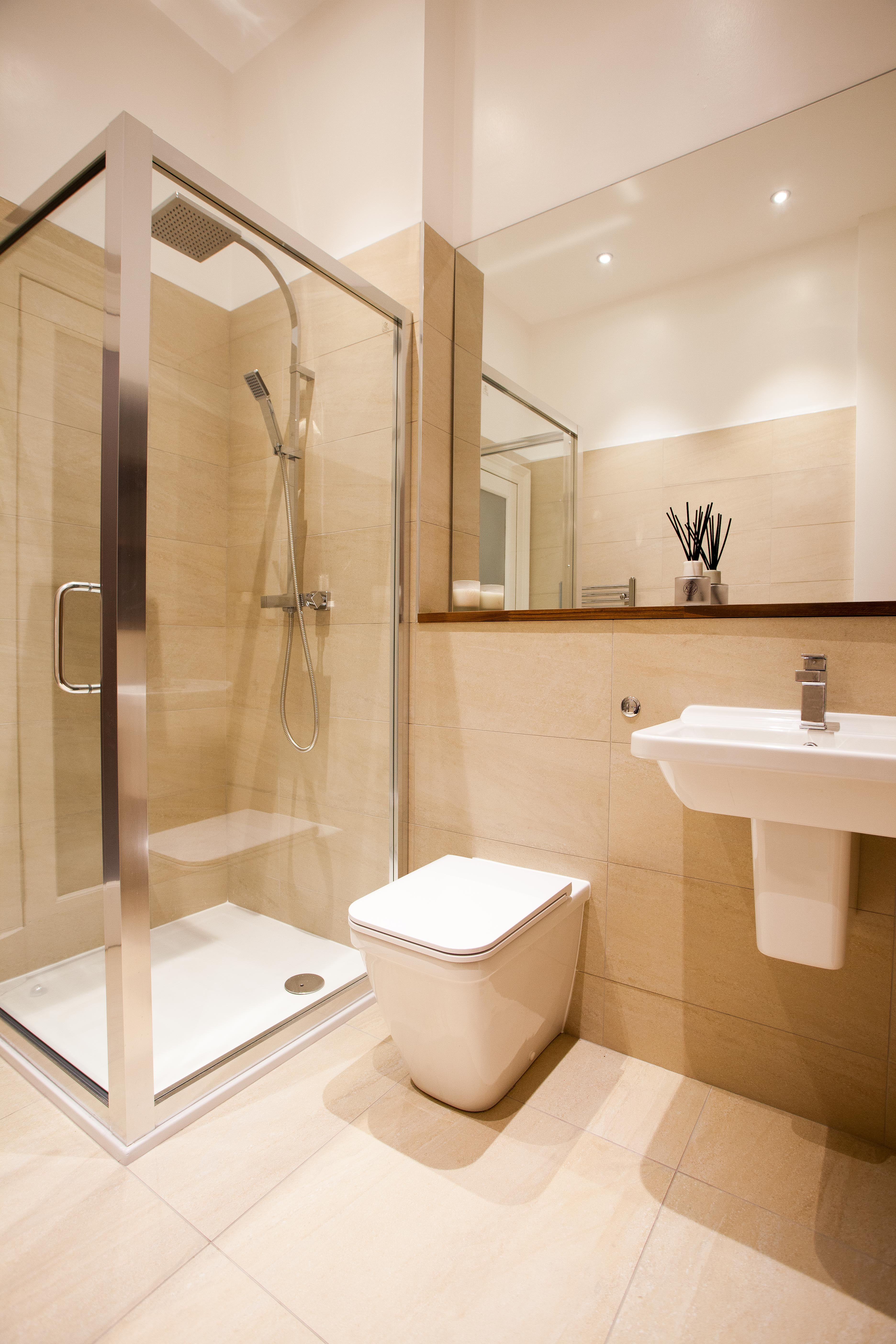 Large shower with low level shower tray, back to wall toilet and semi ped basin.