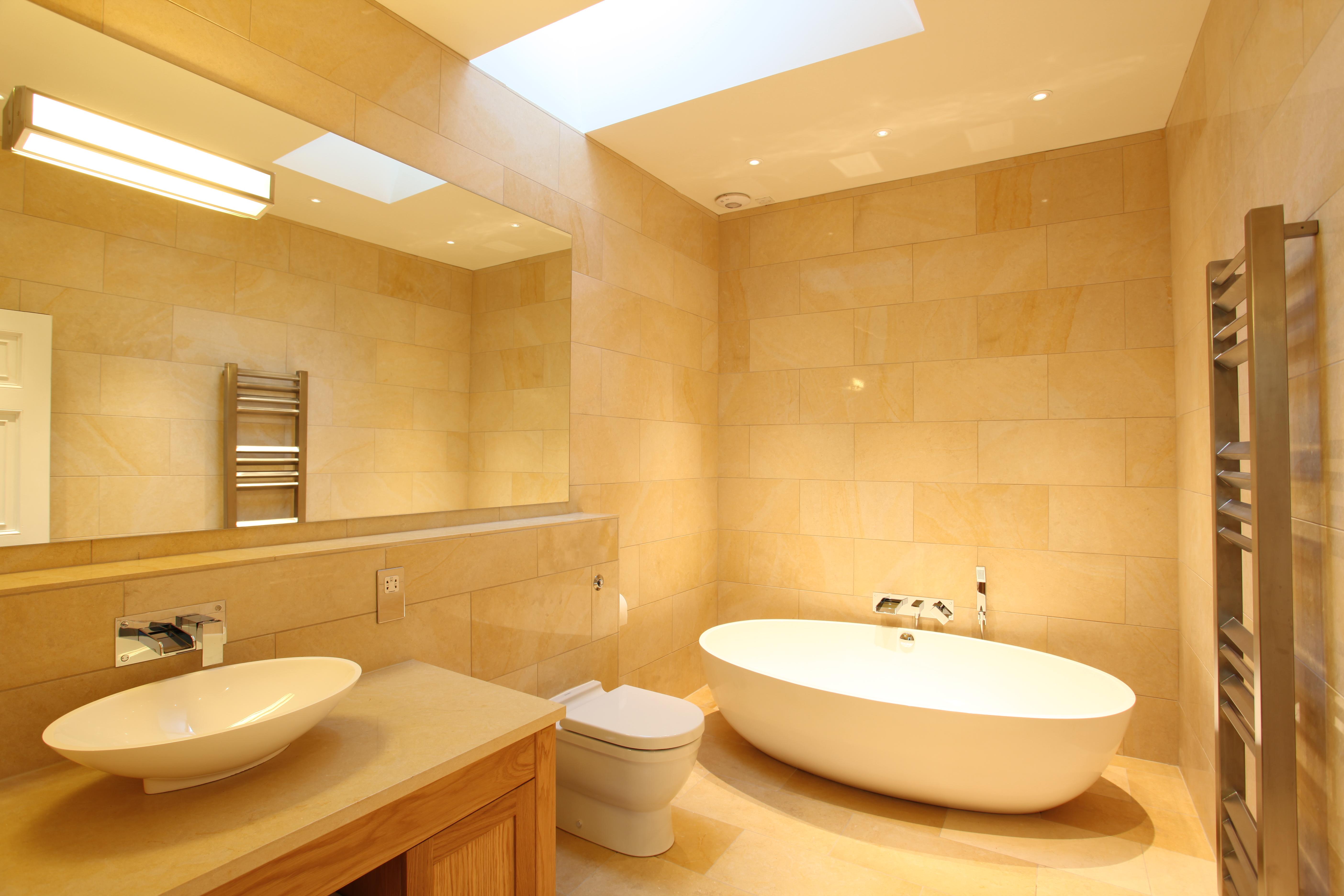 Beige Bathroom with large mirror and freestanding bath in Edinburgh.