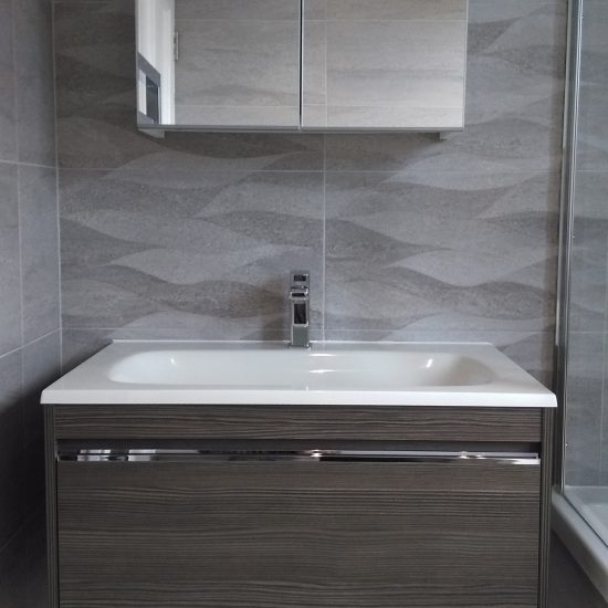 Brown wood vanity unit with drawer, basin and mirror and grey tiles.