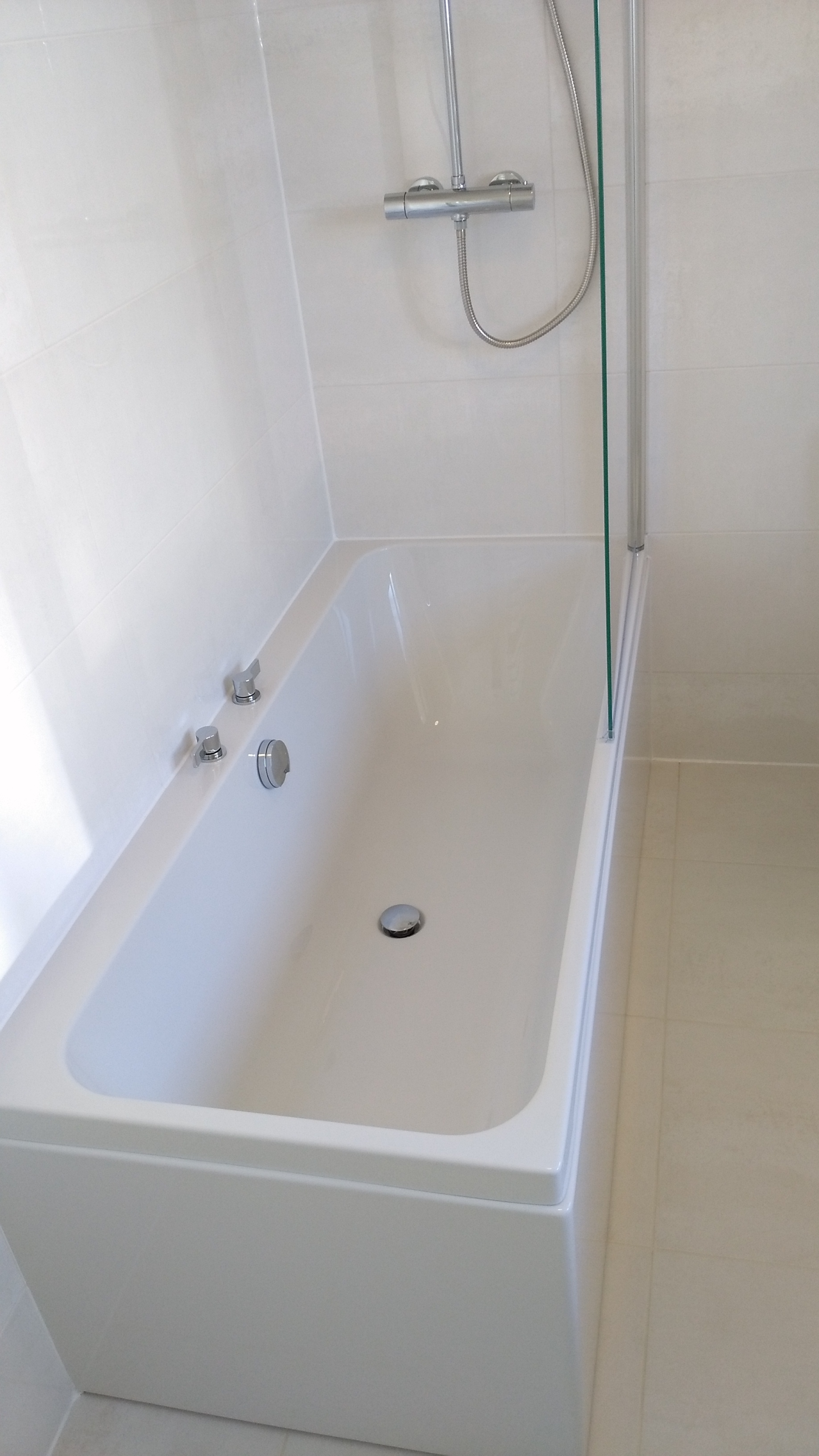 White bath with wall mounted taps