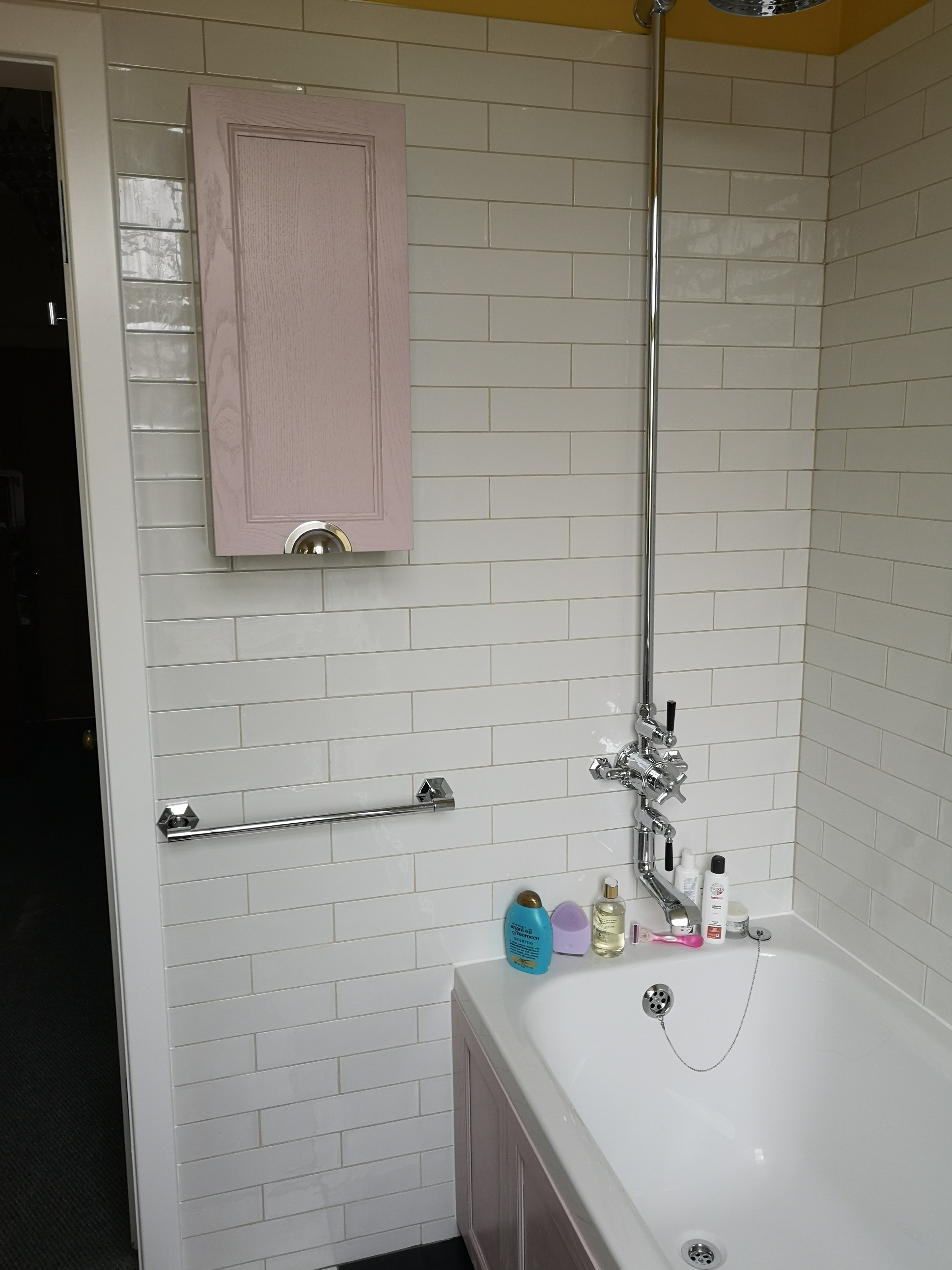 Exposed shower valve with white subway tiles and chequered floor.