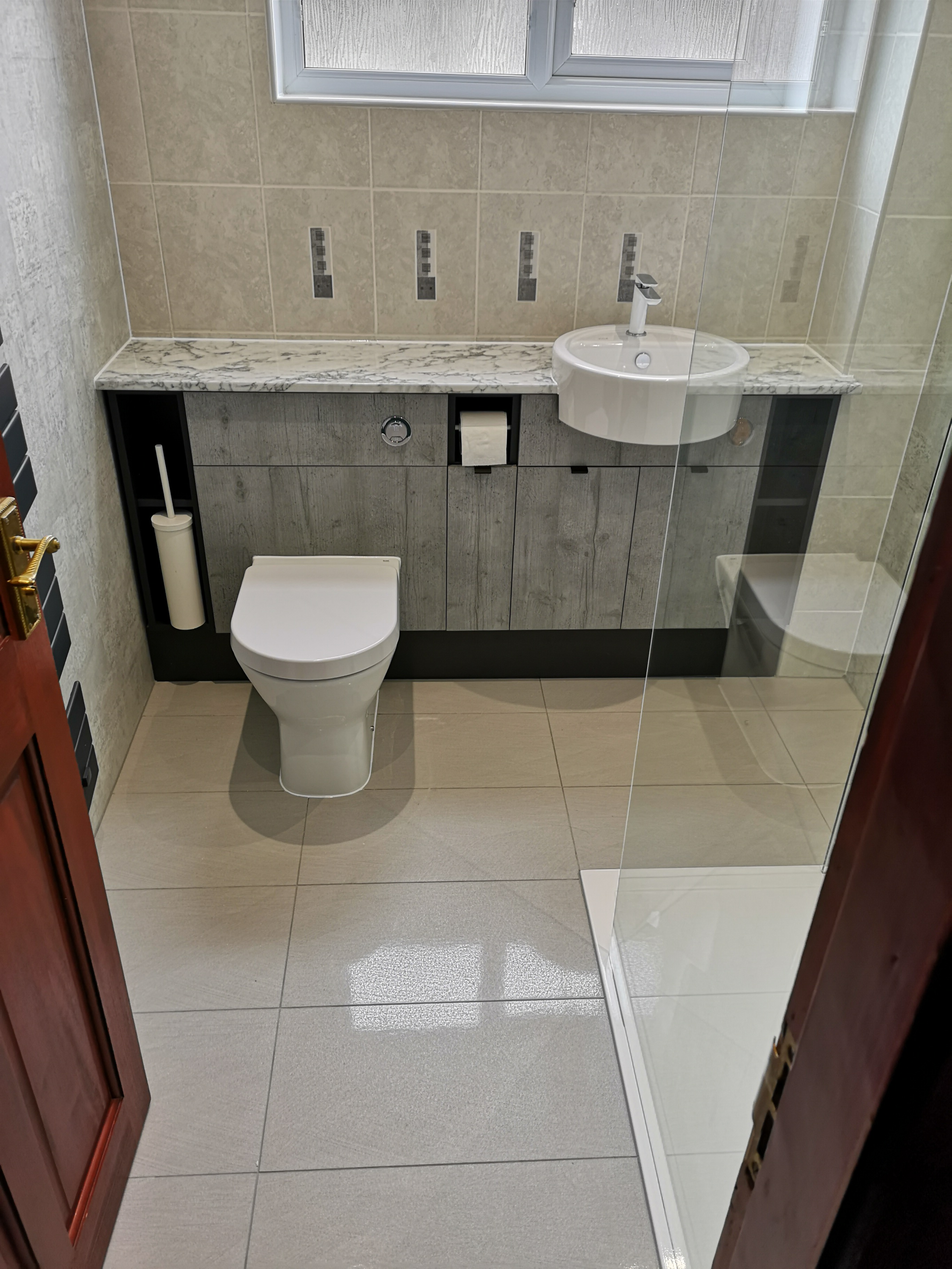 Grey Bathroom gloss wall and floor tiles with WC.