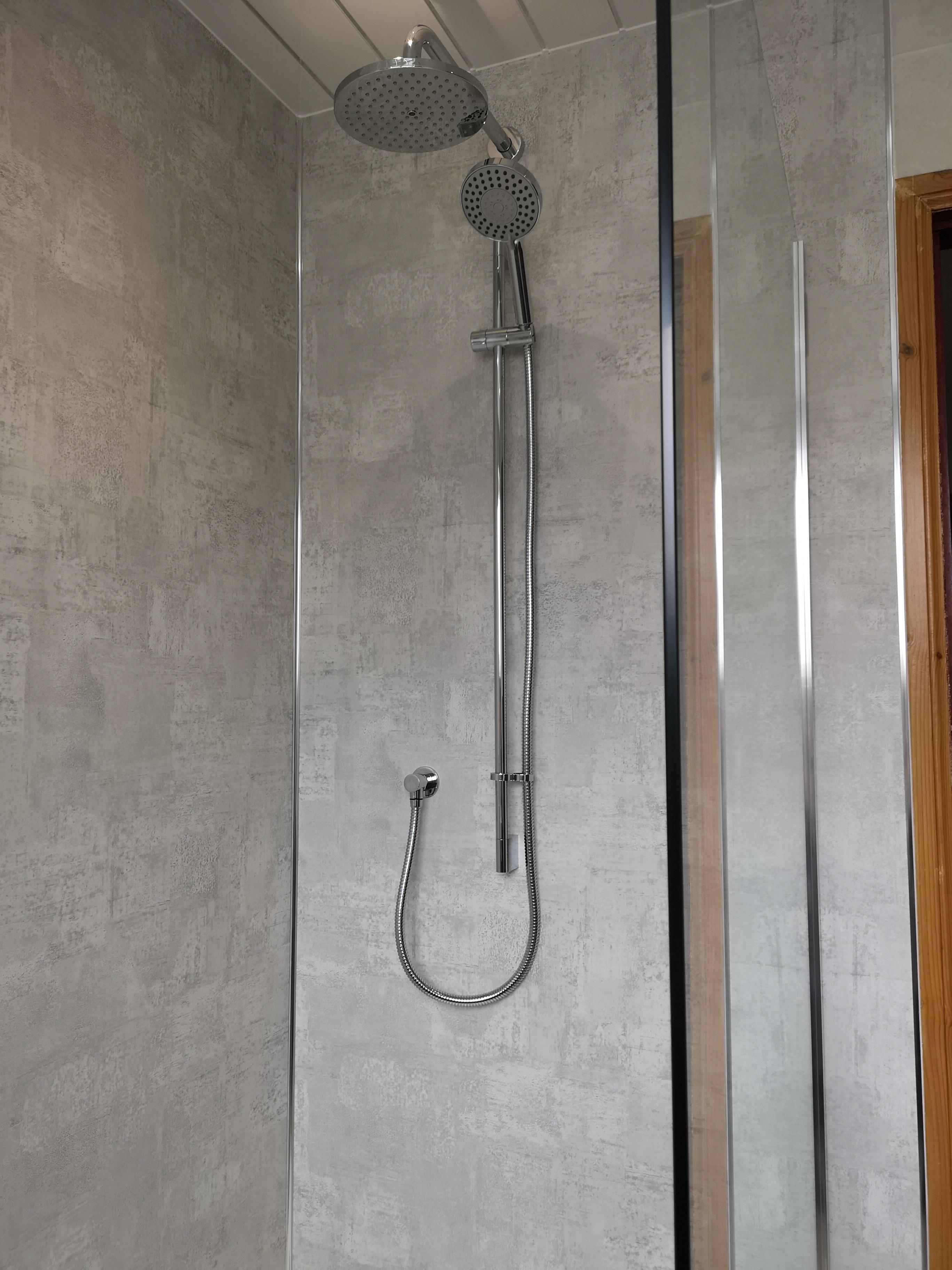 Grey Bathroom gloss wall and floor tiles with shower.