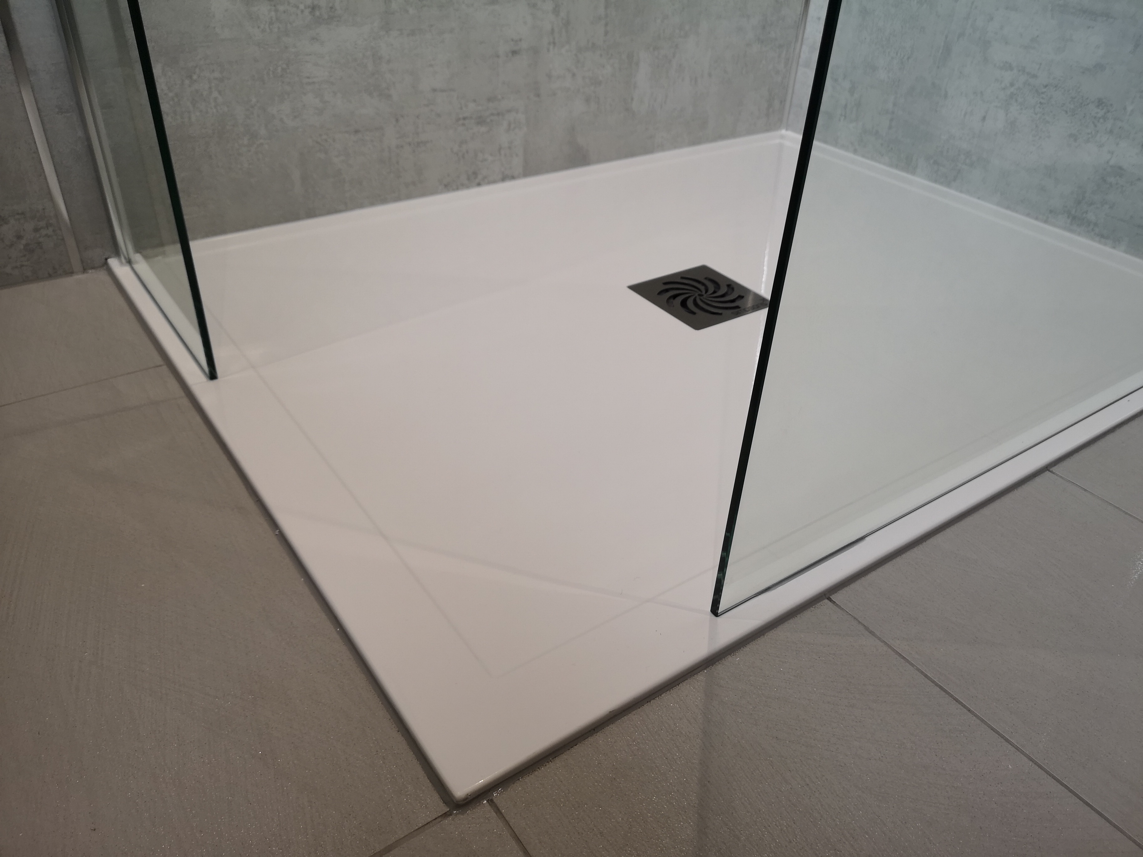 Grey Bathroom gloss wall and floor tiles with low level shower tray.