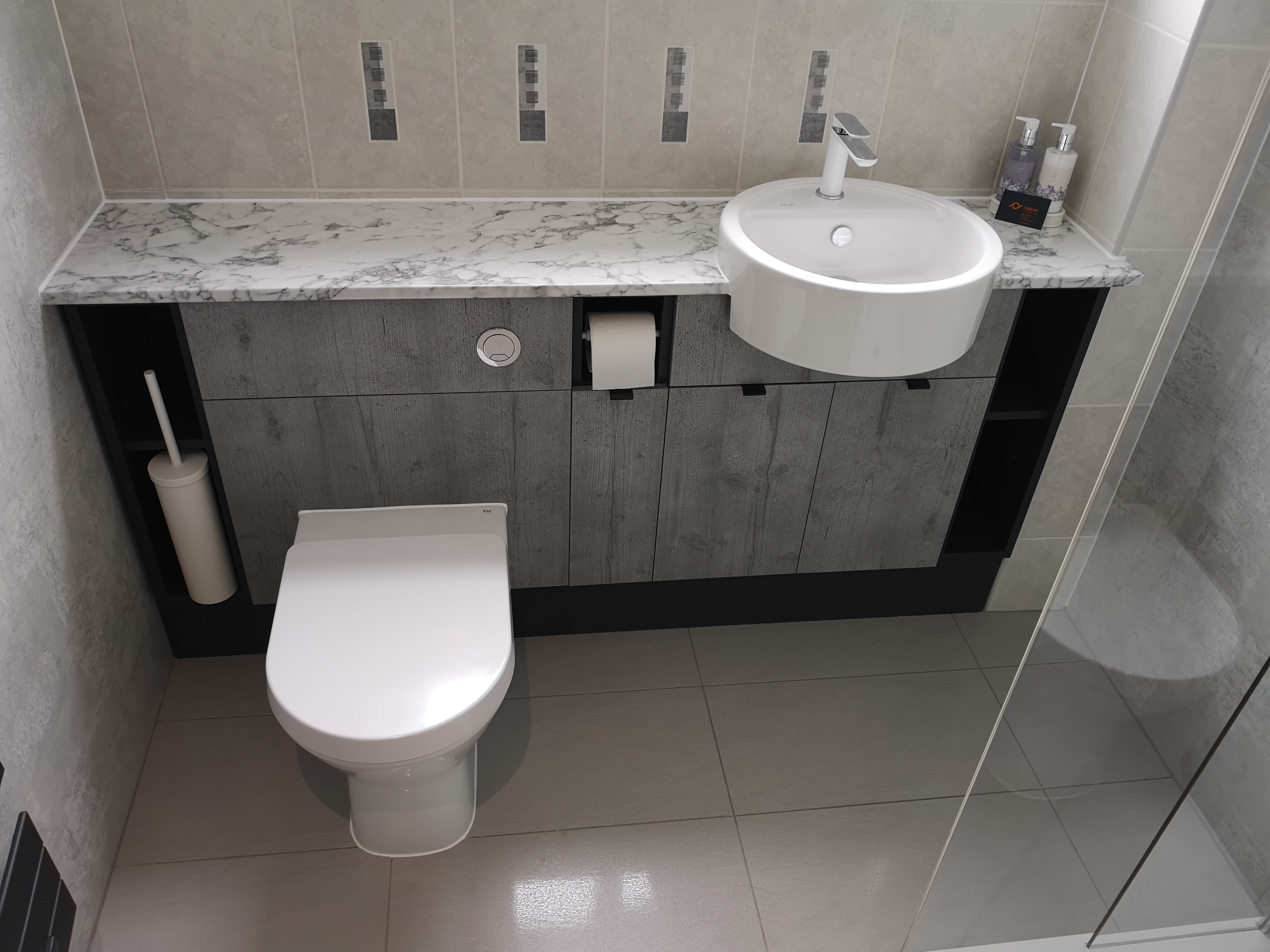 Grey built in vanity unit with basin and toilet