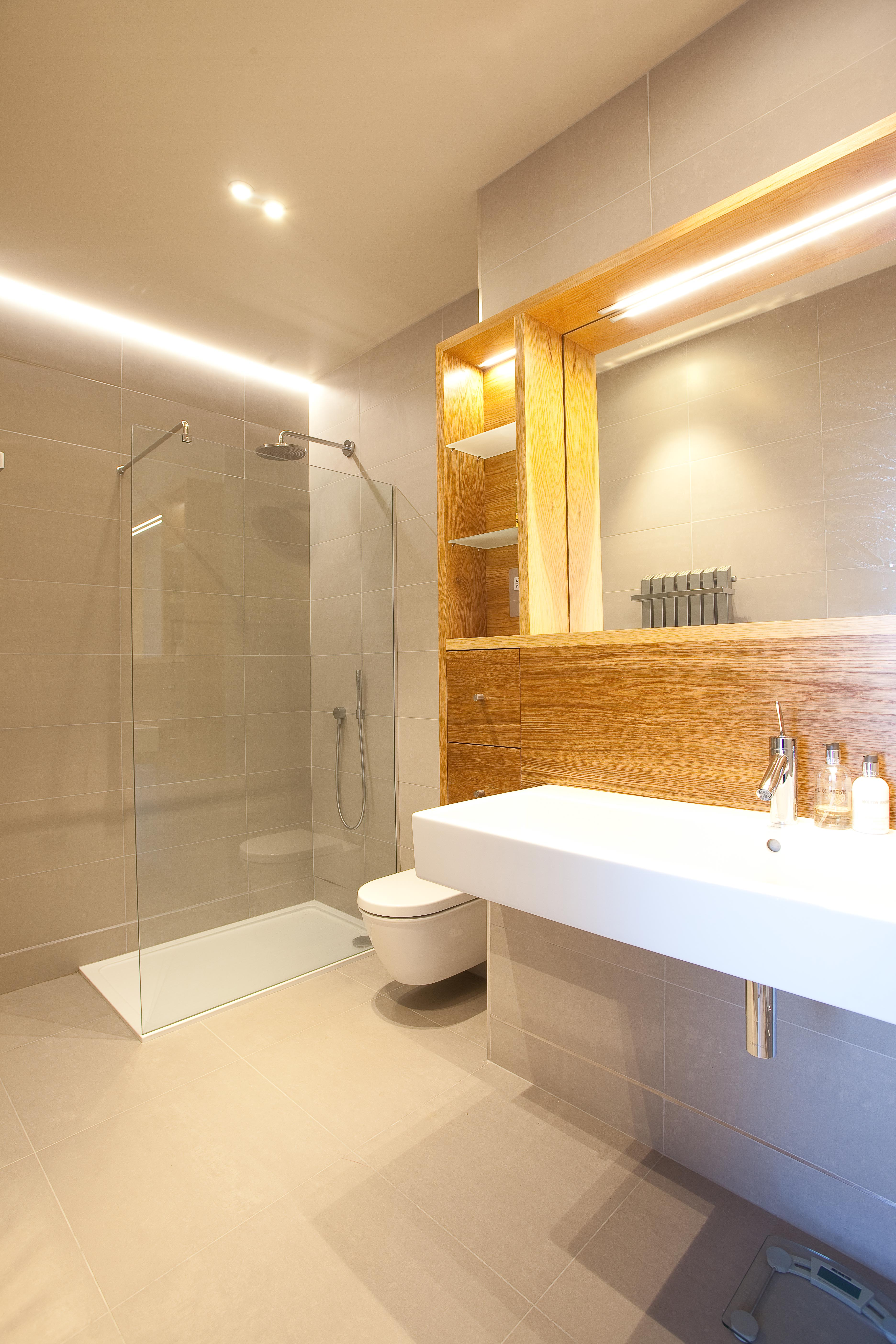 Sleek contemporary white sink with toilet and walk in shower.