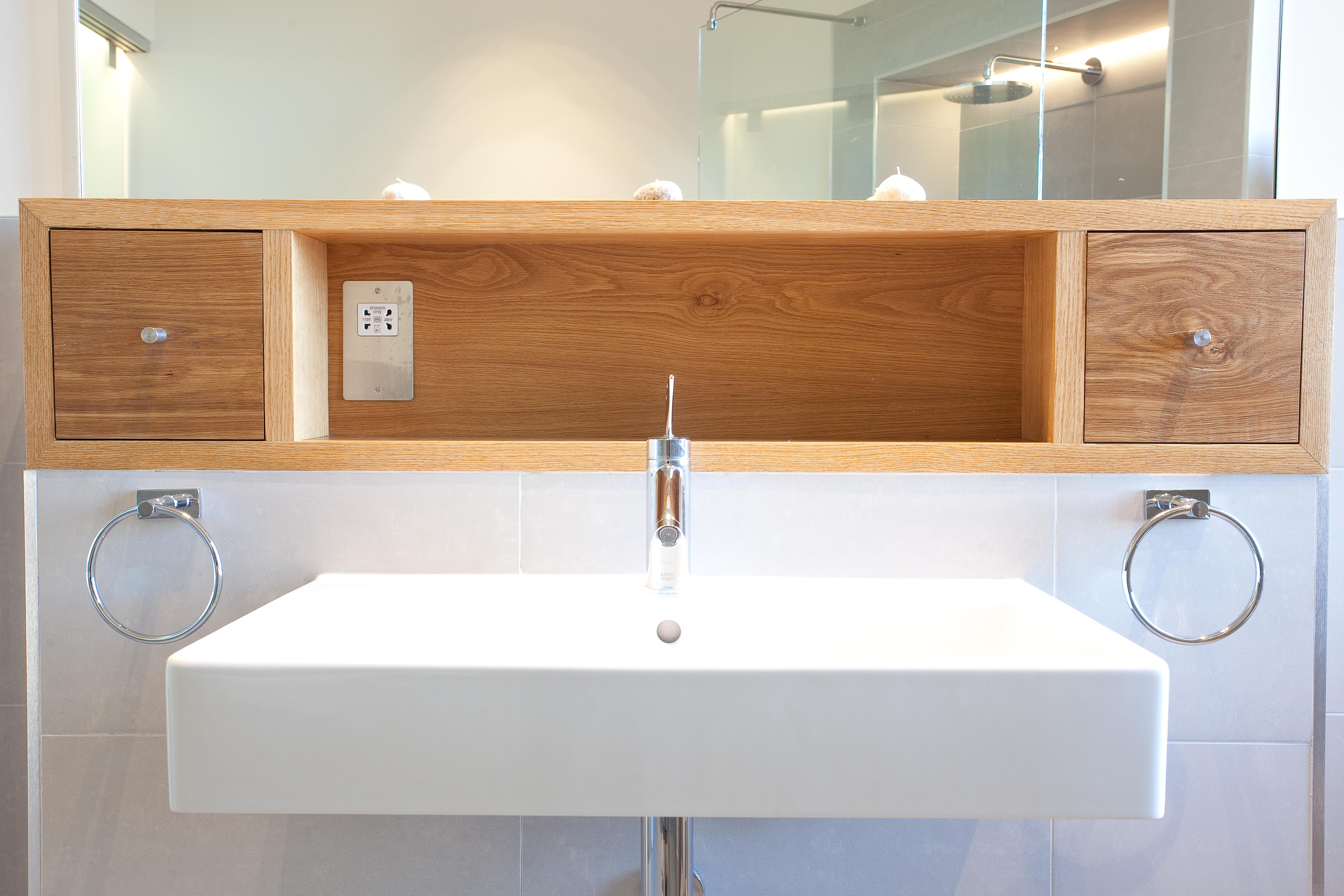 Sleek and contemporary white sink with open wood shelf and mirror above.