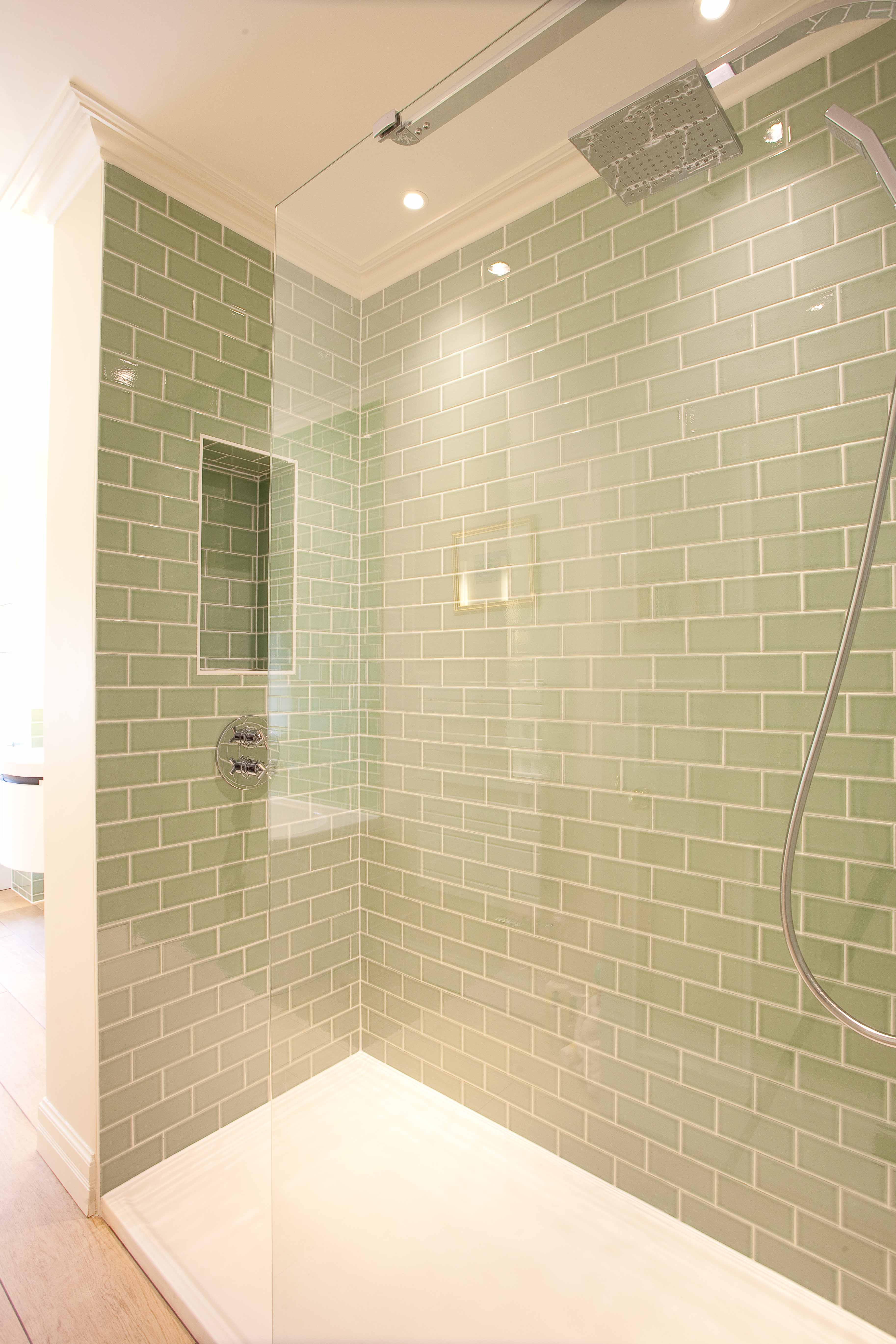 Green subway tiled shower with bespoke glass