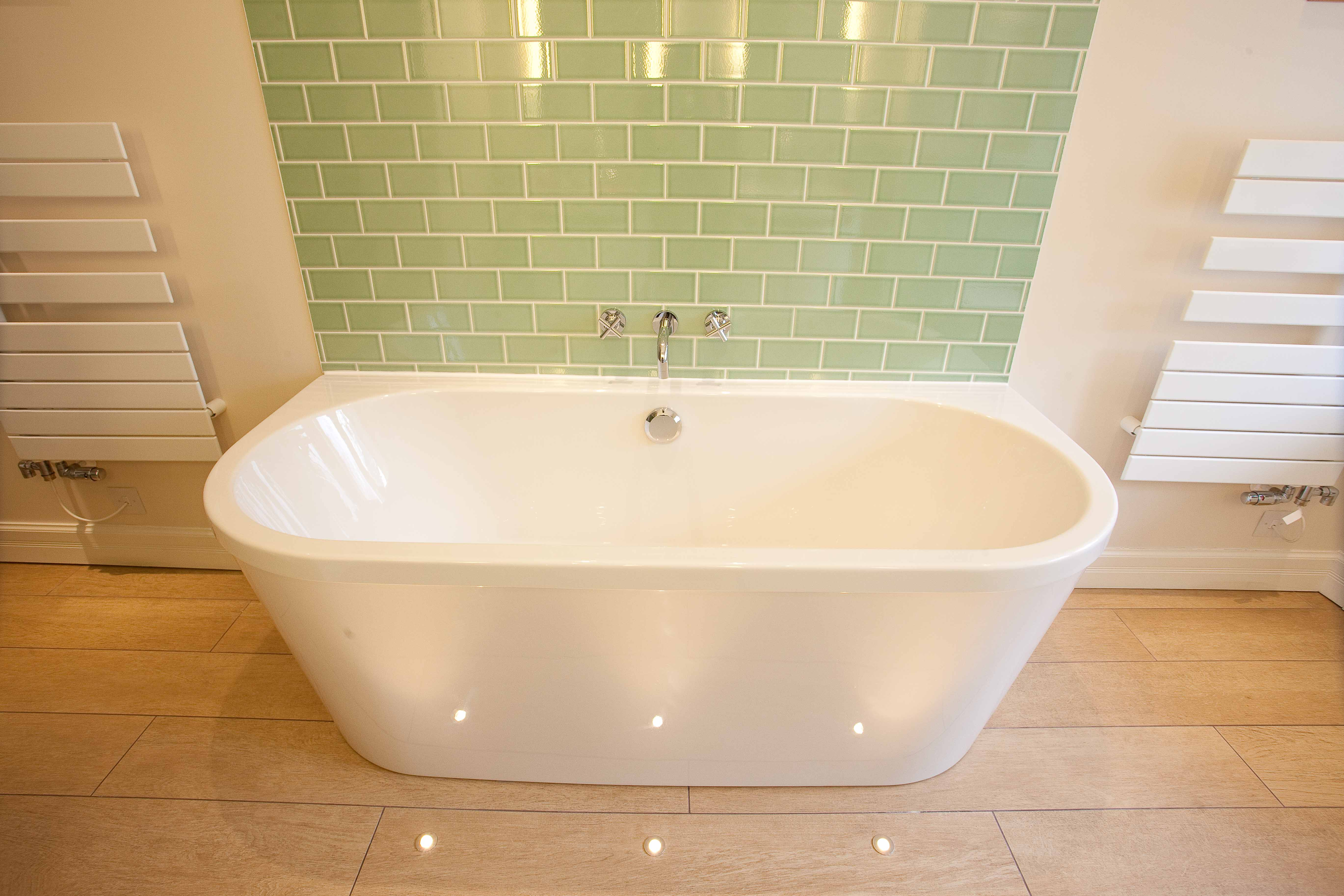 Bath with floor lighting and green subway tiles behind.