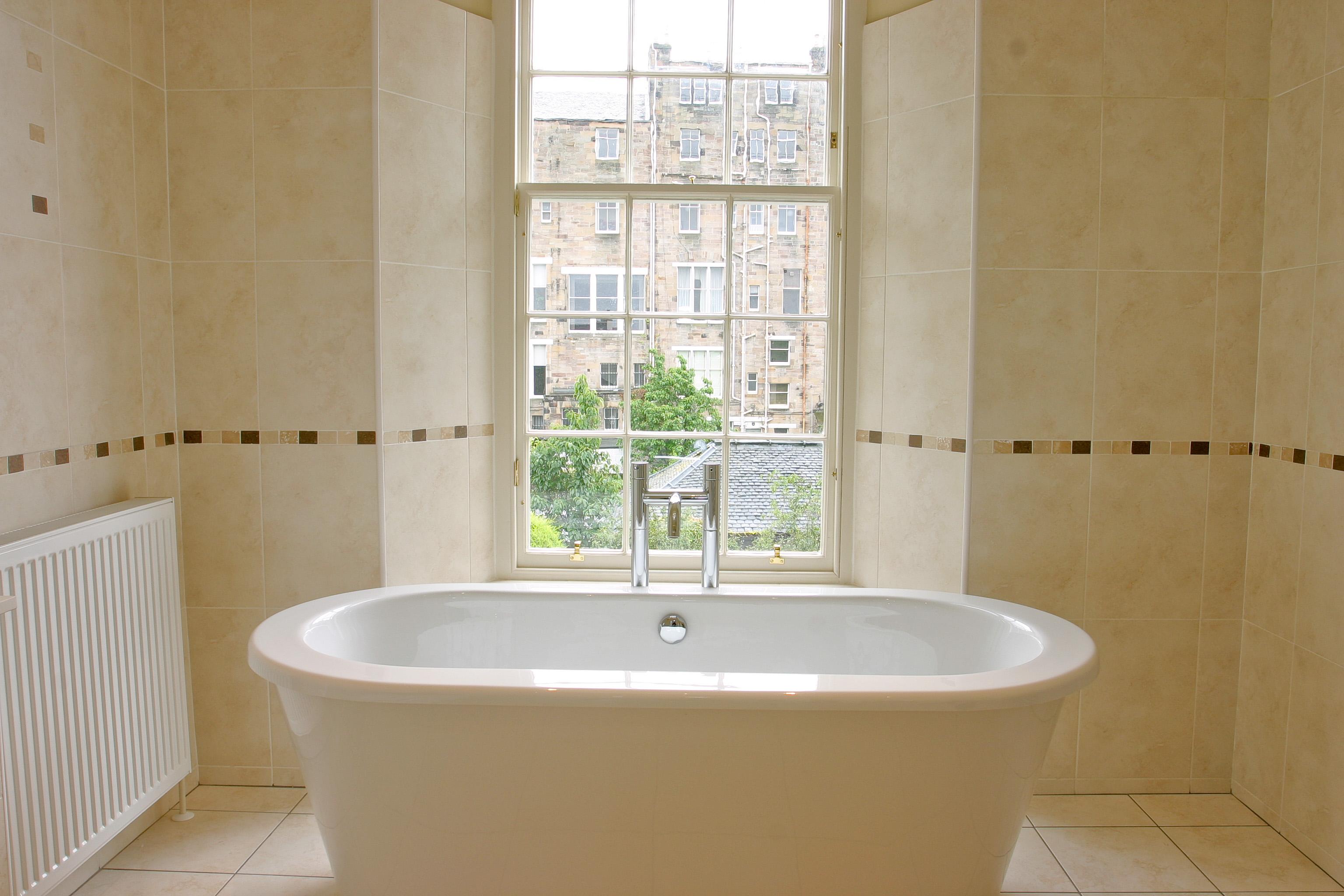 Freestanding plastic bath with floorstanding taps