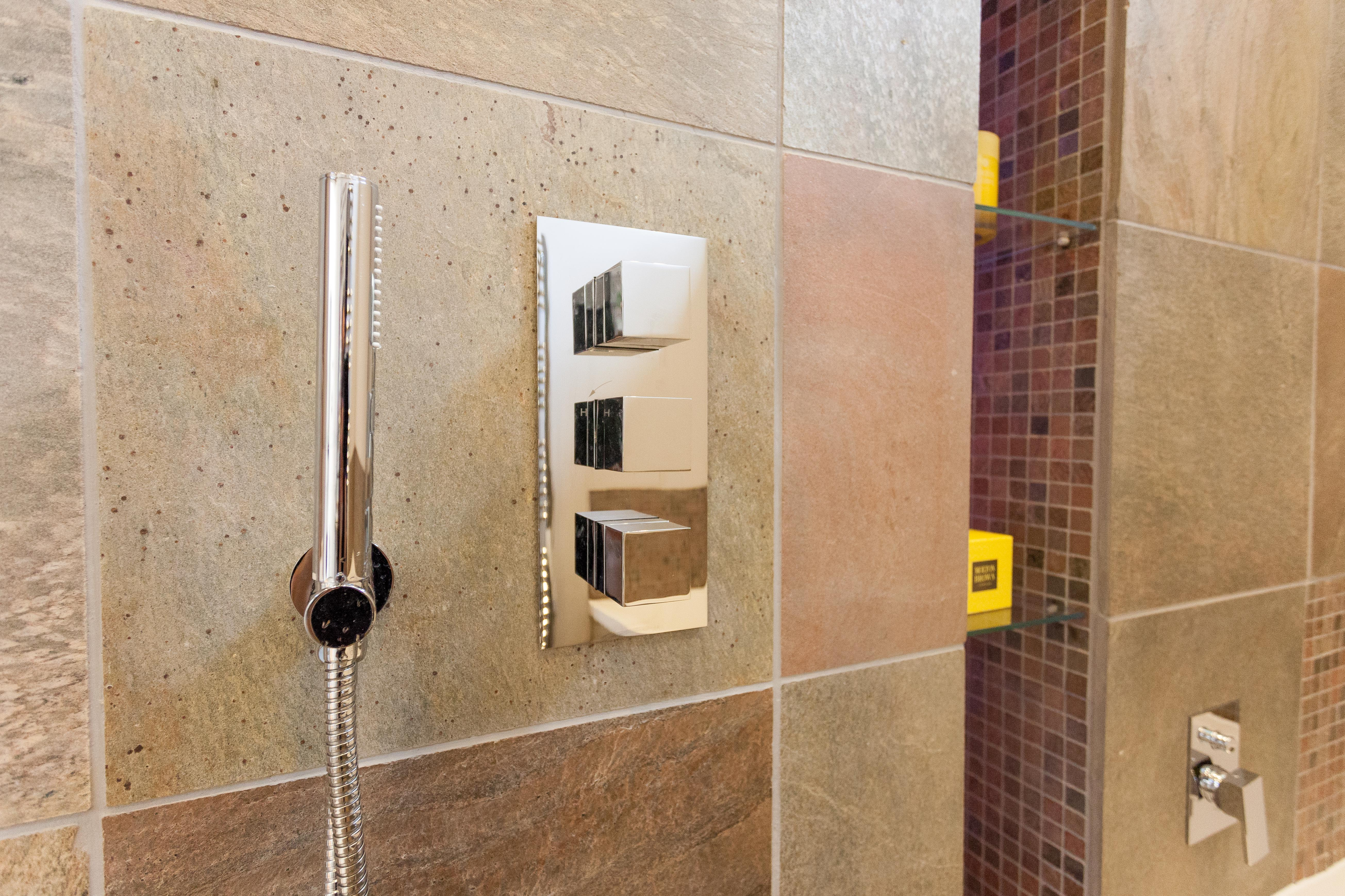 Stone tiles with chrome shower mixer.