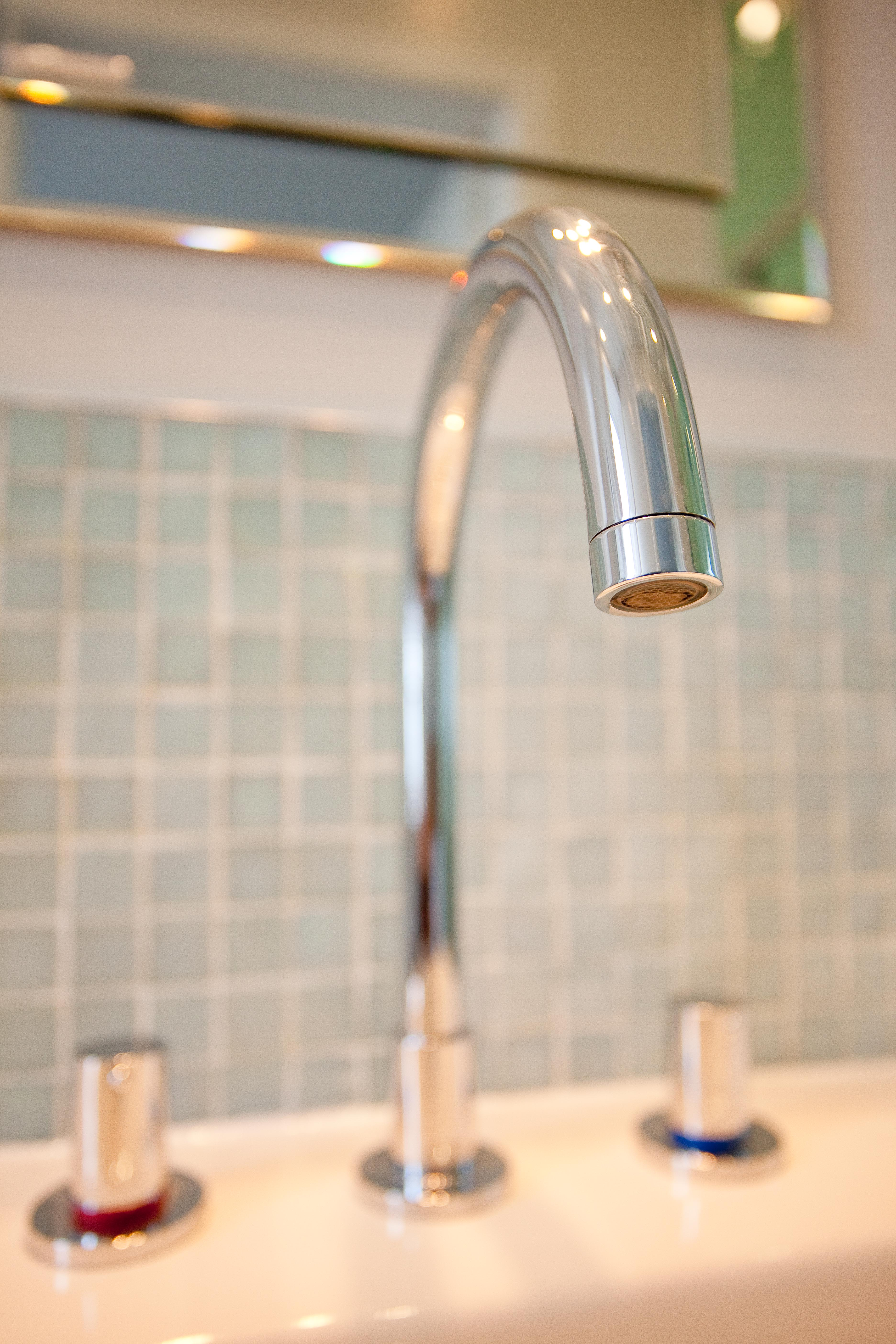 Curved basin tap with mosaic tiles as splashback