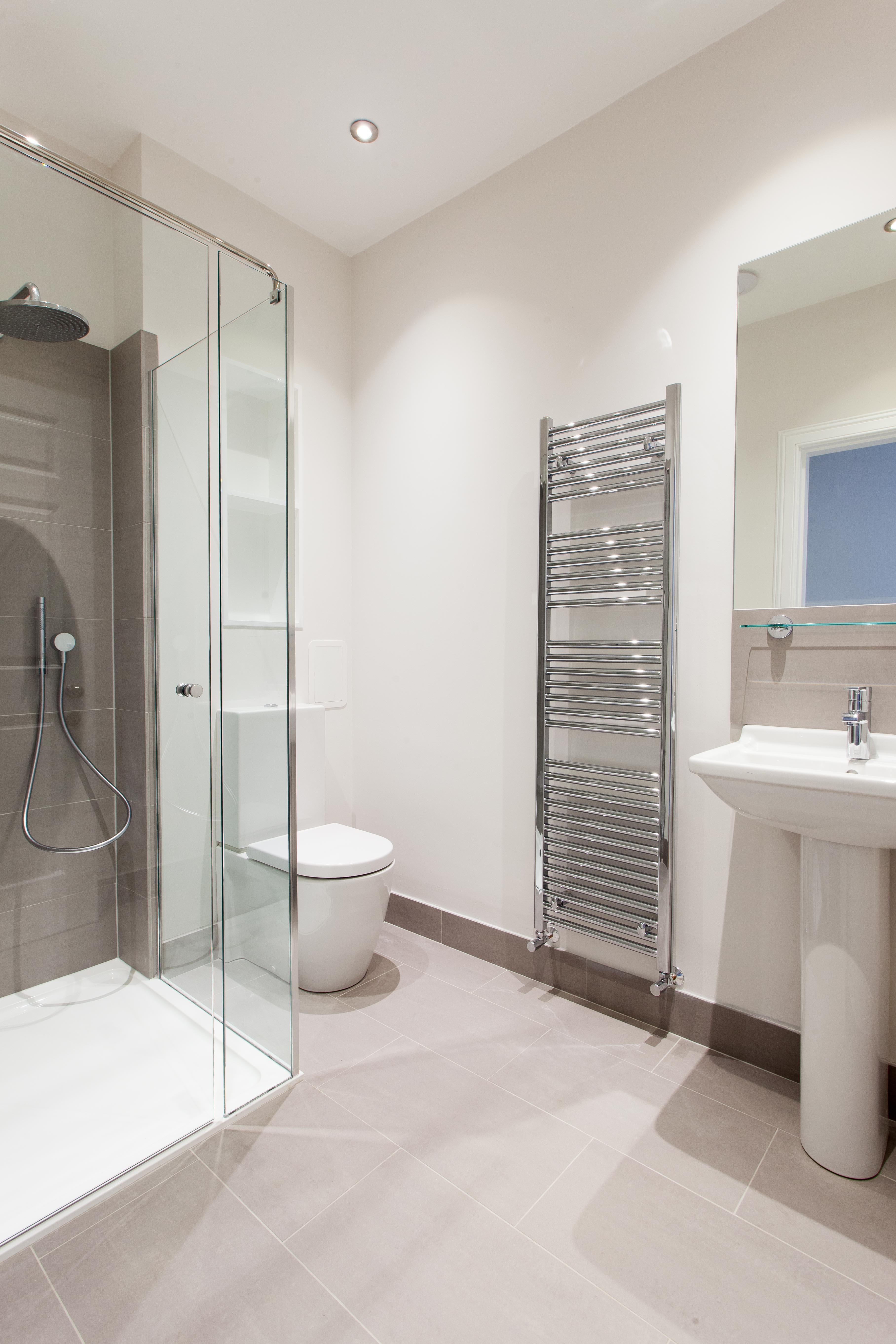 Modern bathroom with tall towel radiator with white tiles.