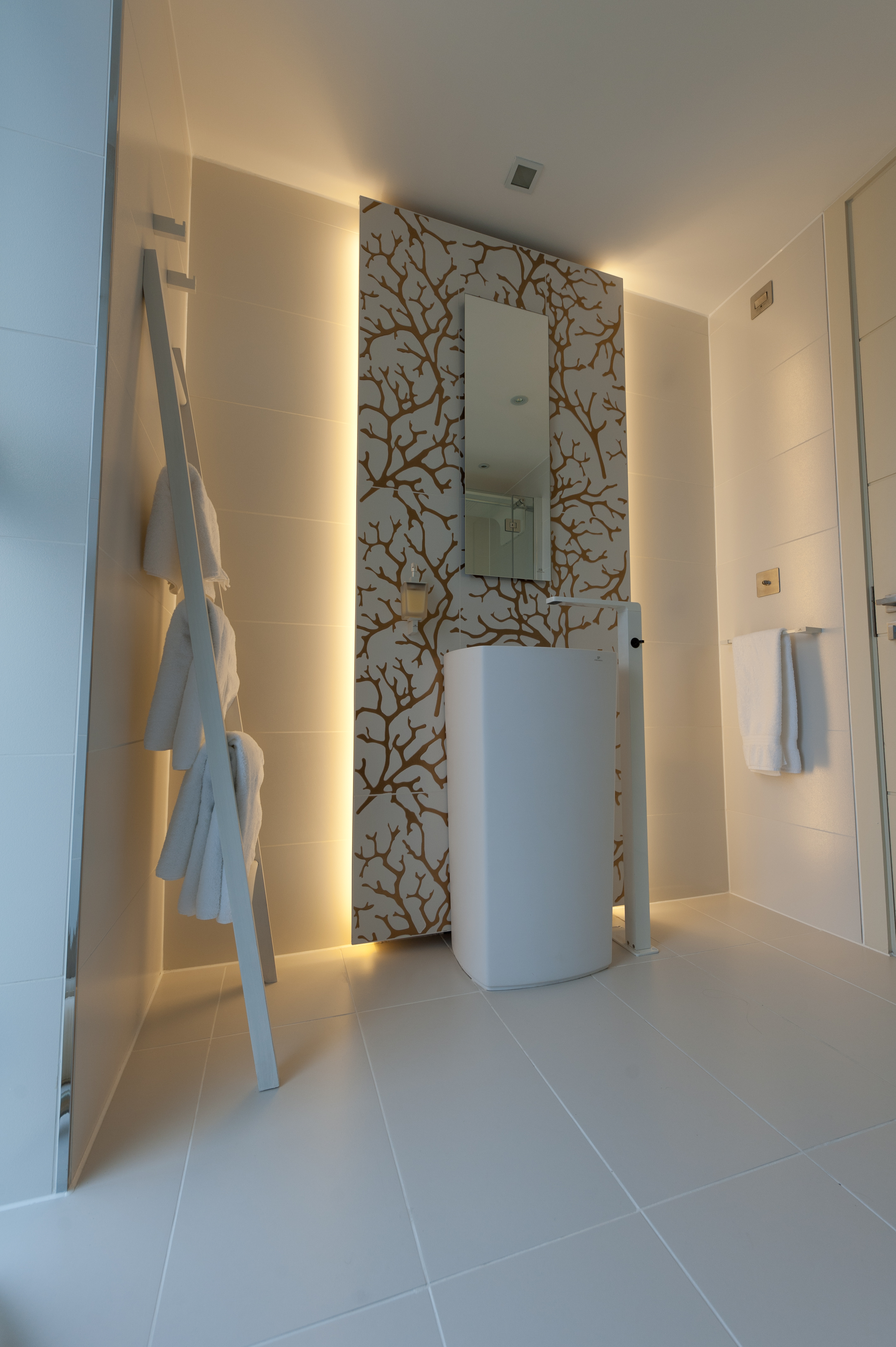 Krion freestanding basin with porcelanosa tiles and LED lighting.